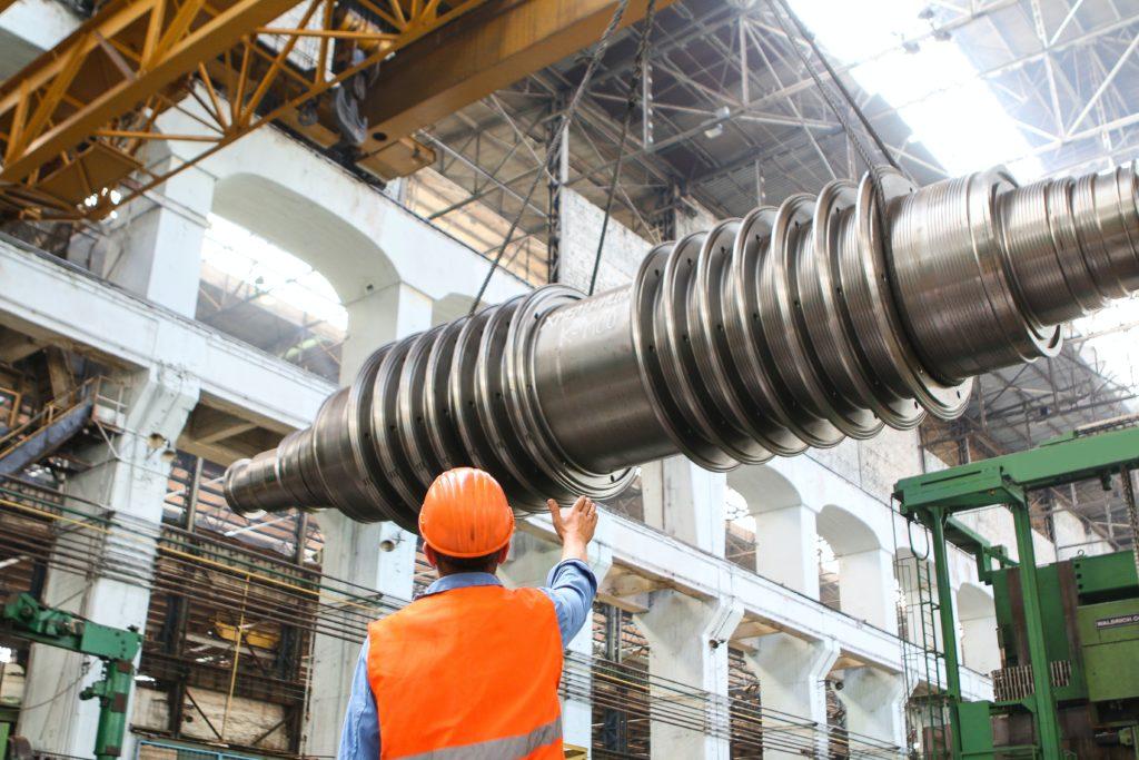 Homme travaillant sur un chantier guidant le transport d'une grande pièce industrielle
