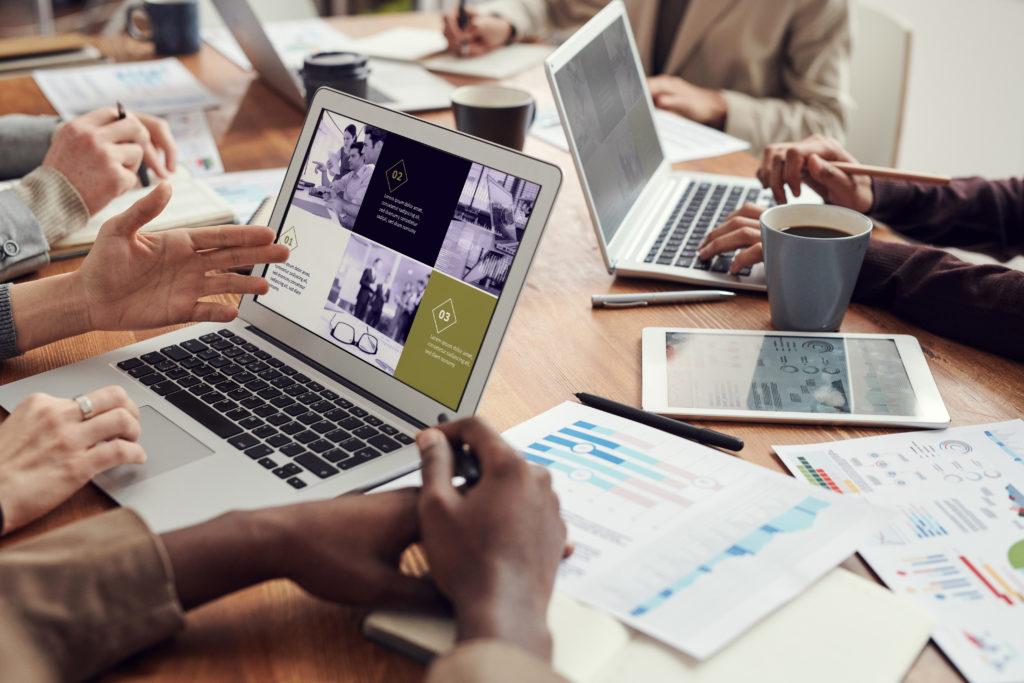 Réunion présentant un document d'ECE GROUPE. Des personnes discutent autour d'une table avec des ordinateurs, tablettes et papiers posés sur celle-ci