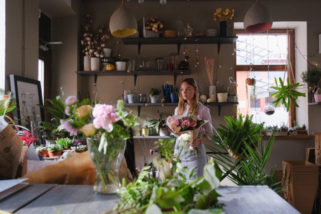 Fleuriste dans sa boutique tenant dans sa main une bouquet de fleur